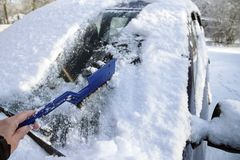 Cleaning the car windshield from snow in winter, safety concept Stock Photos