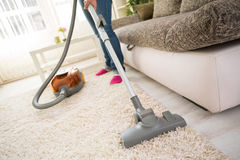 Cleaning carpet in living room. Cleaning carpet with vacuum cleaner in living room Stock Images