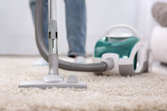 Cleaning carpet with vaccum cleaner. At home Stock Photos