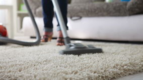 Cleaning the  carpet with vacuum cleaner before couch - close up. Detail stock footage