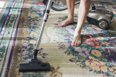 Cleaning carpet with vacuum cleaner in living room Stock Images