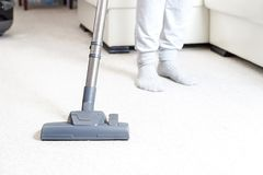 Cleaning the carpet with vacuum cleaner in the living room stock image