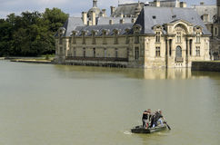 Cleaning the castle lake. Chantilly  is a commune in the Oise department in the valley of the Nonette in the Picardy region of northern France. Surrounded by Stock Photo