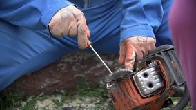 Cleaning chainsaw chain close up slow motion. Removing sawdust from chainsaw with screwdriver in slow motion stock footage