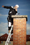 Cleaning chimney. Chimney sweep man in work uniform cleaning brick style chimney on building roof Royalty Free Stock Image