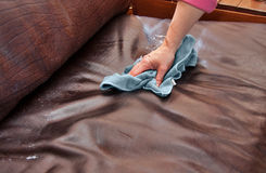 Cleaning chores. Closeup of hand cleaning and conditioning a leather couch with conditioning product and blue microfiber cloth Stock Images