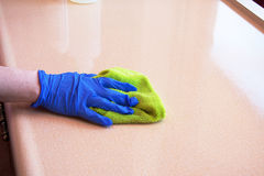 Cleaning chores. Closeup of hand with purple latex glove cleaning  kitchen countertop with green microfiber cloth Royalty Free Stock Images