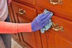 Cleaning chores. Closeup of hand with purple latex glove cleaning  wooden cabinet with green microfiber cloth Royalty Free Stock Photos