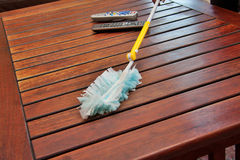 Cleaning chores. Dusting a wooden coffee table with a synthetic duster, closeup perspective shot Stock Images