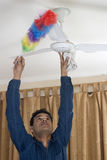 Cleaning the cieling fan Stock Image