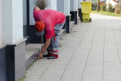 Cleaning of a city street - the worker the yard keeper in a uniform collects garbage by hands near a building. Cleaning of a city street - the worker the yard Royalty Free Stock Image