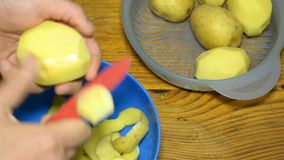 Cleaning or cleaning the potatoes before cooking. Human hands peel potatoes with a red kitchen knife. Close-up stock footage