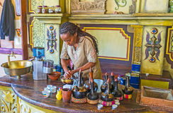 Cleaning coffee beans for Ethiopean ceremony. KIEV, UKRAINE - JUNE 4, 2017: The young Ethiopian Tigrayan woman cleans coffee beans for the traditional coffee Stock Photography