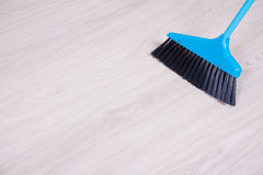 Cleaning concept - blue broom sweeping floor Stock Photography