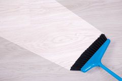 Cleaning concept - blue broom sweeping floor Royalty Free Stock Image