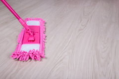 Cleaning concept -close up of mop on wooden floor Stock Images