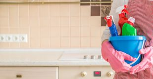 Cleaning concept - female holding cleaning supplies in blue basket stock photography