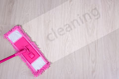 Cleaning concept - pink mop on wooden floor with word cleaning Royalty Free Stock Image