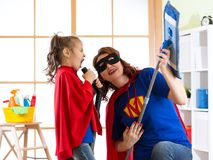 Cleaning concept. Super hero woman and daughter playing guitar and singing on cleaning equipment. Family ready to Stock Images