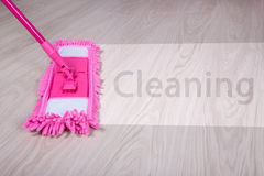 Cleaning concept - wet mop on wooden floor with word cleaning Stock Image