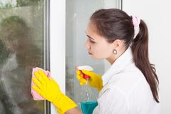 Cleaning concept. Young woman washing window stock image
