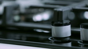 Cleaning the coocktop button on gas cooker. Close up shots of kitchen activities while turning on and off fire on gas cooker cooktop stock footage
