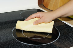Cleaning the cooktop. Woman's hand with a cloth cleaning ceramic cooktop Stock Photo