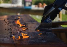 Cleaning countertop from old paint with fire. woodworking, restoration of old furniture royalty free stock photography