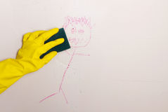 Cleaning crayon off wall with sponge Royalty Free Stock Photos