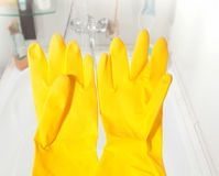 Cleaning day!. Yellow gloves against a bath - time to clean your home up Royalty Free Stock Images