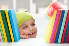 Cleaning day - boy dusting books. Cleaning day - boy with head scarf dusting books stock photography