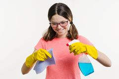 Cleaning day, spring cleanup, housework concept. Girl teenager in yellow gloves with rag and spray detergent. royalty free stock images