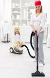 Cleaning day - woman and little girl tidy the room Stock Image