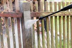 Cleaning dirty garden fence post with high pressure washer Stock Photos