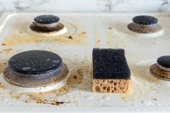 Dirty gas stove. cleaning the kitchen. Cleaning a dirty modern kitchen gas stove with a sponge stock image