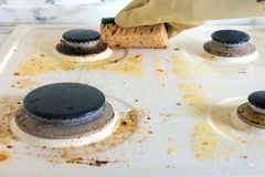 Dirty gas stove. cleaning the kitchen. Cleaning a dirty modern kitchen gas stove with a sponge royalty free stock photos