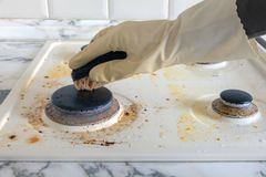 Dirty gas stove. cleaning the kitchen. Cleaning a dirty modern kitchen gas stove with a sponge stock images