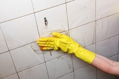 Cleaning of dirty old tiles in a bathroom Stock Photos