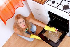 Cleaning the dirty oven. Lovely woman wearing yellow gloves cleaning the dirty oven Royalty Free Stock Photography