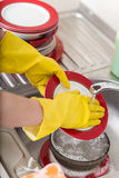 Cleaning dishware kitchen sink sponge washing dish. Close up of female hands in yellow protective rubber gloves washing Stock Images