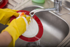 Cleaning dishware kitchen sink sponge washing dish. Close up of female hands in yellow protective rubber gloves washing Stock Photo