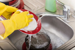 Cleaning dishware kitchen sink sponge washing dish. Close up of female hands in yellow protective rubber gloves washing Stock Photos