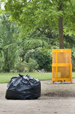 Cleaning and Environment. This image shows a large trash bag and a garbage can in a garden Stock Photos