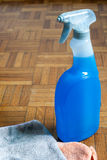 Cleaning equipment. Liquid cleaner and dust cloths on a wood flooring (parquet Royalty Free Stock Image