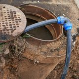 Cleaning equipment in a sewer manhole Royalty Free Stock Image