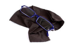 Cleaning eye glasses. Blue glasses and an off-black fine fabric optical glass cleaner Royalty Free Stock Photography