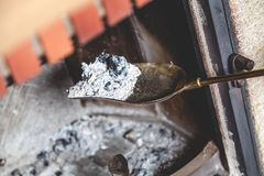 Ash from fire lay extinguished on brass blade. Cleaning the fireplace. Ash and charred piece of wood lying on the blade with a long handle closeup stock images