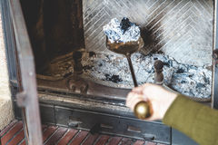Cleaning  fireplace. hand holding  shovel with ash Stock Photos