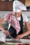 Cleaning the fish. Pretty young female chef cleaning the trout Stock Photo