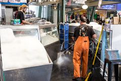 Cleaning a fish store with pressure washer. Seattle, Washington, USA - September 4th, 2017: Male worker wearing a waterproof fishing pants is cleaning the floor Stock Photography